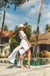 beautiful girl posing in white dress at swimming pool at the resort
