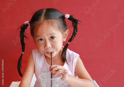 Photo  Close up little girl using straw to drink water from plastic cup in the restaurant