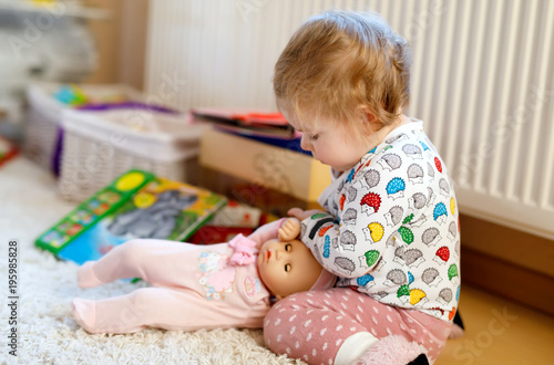 Photographie Cute adorable baby girl playing with first doll