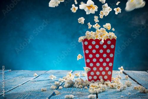 Box of popcorn on blue background.