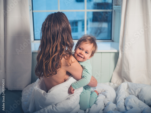 Mother embracing little boy in morning Canvas Print