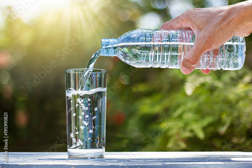 Hand holding drinking water bottle pouring water into glass on wooden table on blurred green nature background