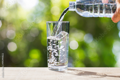 Fototapeta Hand holding drinking water bottle pouring water into glass on wooden tabletop on blurred green bokeh background with soft sunlight obraz na płótnie