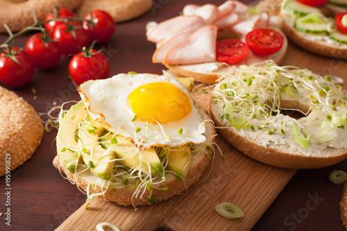 Photo variety of sandwiches on bagels: egg, avocado, ham, tomato, soft cheese, alfalfa