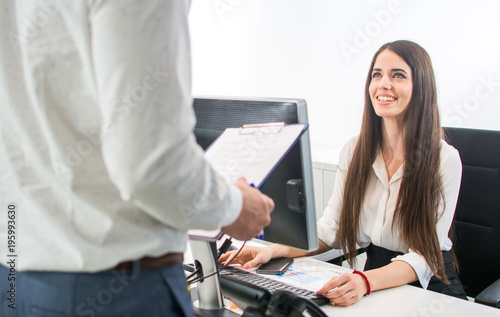 Fotografija Beautiful smiling secretary welcoming client at office reception desk