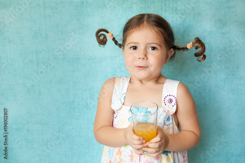 Smiling girl with funny pigtails with glass of juice Wallpaper Mural
