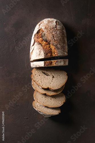 Printed kitchen splashbacks Bread Loaf of fresh baked artisan sliced rye bread over dark brown texture background. Top view, copy space.