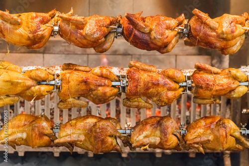 Valokuva  Grilled chickens on a spit, background