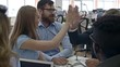 Medium shot of colleagues sitting at table in office and giving high five to each other when discussing project