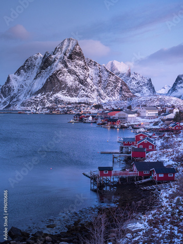 Wall Murals Arctic vertical image of winter scene in reine fishing village in arctic norway, typical red huts and steep snow covered mountains