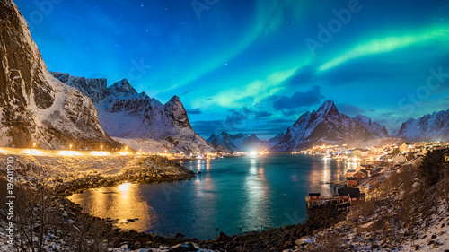 Photo sur Toile Marron chocolat giga panorama with green northern lights over the fishing village of reine on lofoten islands in norwaym snow covered mountains winter landscape and city lights