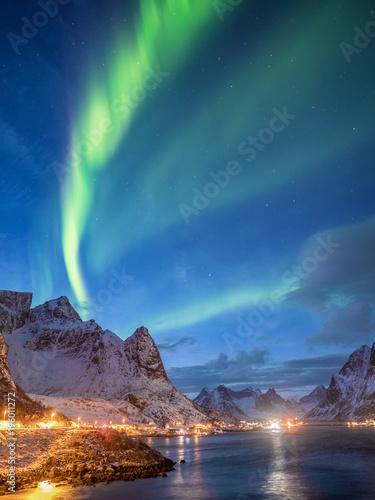Fényképezés aurora borealis over norwegian snow covered mountains and illuminated road