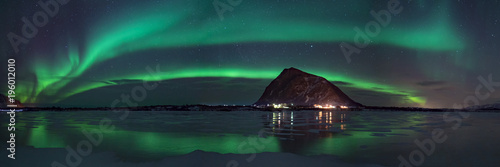 Poster Aurore polaire panorama view of northern lights / aurora borealis on dark sky over mountain in arctic norway, reflection on frozen lake