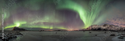 Papiers peints Aurore polaire super wide panorama from arctic norway, frozen lake and aurora borealis dancing in the sky, winter landscape and illuminated mountaisn
