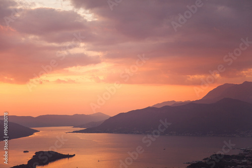 Poster Koraal Amazing sunset landscape with sea, mountains, colorful pink, orange and purple cloudy sky. Beautiful The Boka Kotor Bay and Tivat view in Montenegro. Nature background.