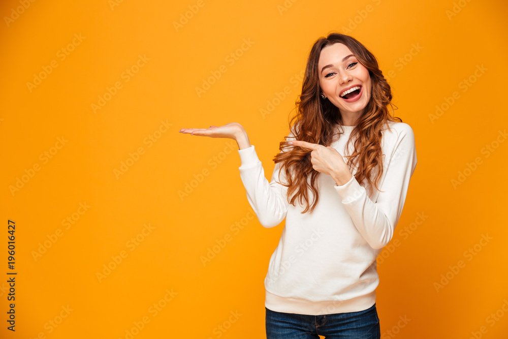 Fototapety, obrazy: Pleased brunette woman in sweater holding copyspace on the palm