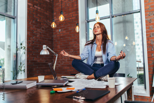 Fotografie, Obraz  Female student sitting in lotus pose on table in her room meditating relaxing af