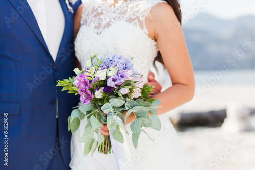 Fotografia Bride and groom hold wedding bouquet from blue hydrangea, pink, lilac flowers outdoor