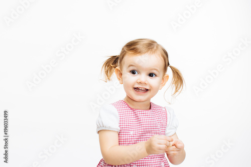 Fotografía  Portrait of an excited toddler girl with ponytails, isolated on white