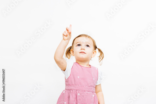 Fotografie, Obraz  Portrait of a preschool toddler girl with ponytails pointing up on white backgro