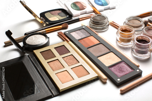 Fototapeta Flat lay of eyeshadow palettes, highlighters and cosmetic brushes on a white bac