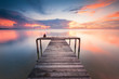 wooden jetty toward horizon during sunset with reflection.