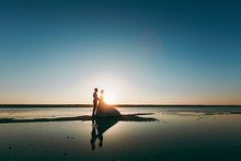 Beautiful Wedding Photosession. Silhouettes Of The Young Bride And Groom In A Long Lush Dress On A Coastline Near The Sea Against A Backdrop Of A Bright Sunset In Evening Sunset