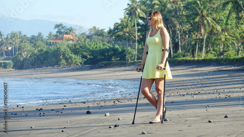 Fényképezés Lady in a yellow sundress with crutches looking into the distance on sandy beach