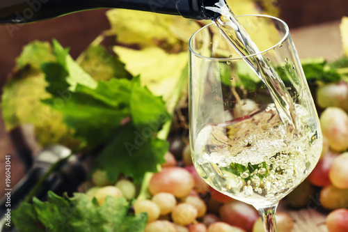 Fototapeta White wine being poured into a glass, vintage wood background, selective focus obraz