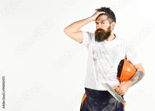 Fotografía  Man with painful face touches forehead. Builder, plasterer,