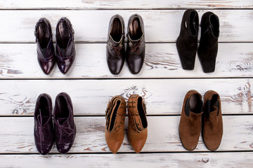 Set of pairs of women's shoes. Wooden desks surface background.