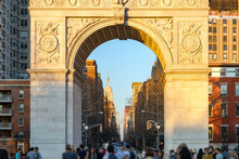 People In Washington Square Park At Sunset With View Of Midtown Skyline In New York City