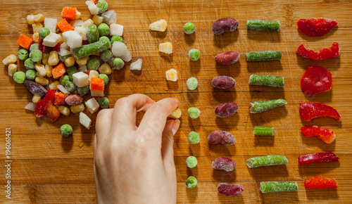 Photo woman's hand collects even row of colorful Frozen mixed vegetables on a wooden background
