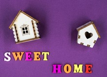 "The Phrase ""Sweet Home"" Laid Out On A Pink Background With Two Toy Wooden Houses."