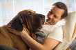 canvas print picture - Portrait of Pretty young, happy, man with beautiful big dog Fila Brasileiro