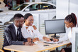 happy African couple and female seller sit at table and make a deal for sale of car