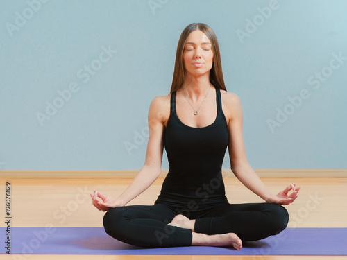 Young fit woman sitting in pose of lotus on yoga mat