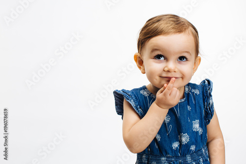 Photographie  Make a wish - Small child with finger on mouth looking up, isolated on white bac
