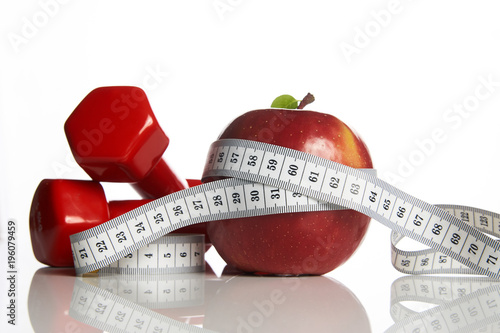 Red apple with measuring tape and red weight dumbbells for
