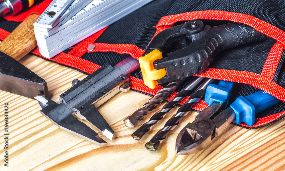tools in tool belt on wood planks with copy space - obrazy, fototapety, plakaty