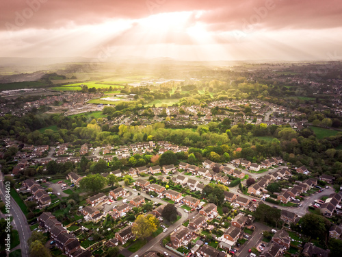 Photo Sun bursting through clouds over traditional British houses with countryside in the background