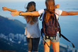 Two young women with open arms on a top of mountain looking from above on Rio de Janeiro panorama at sunset, Pedra Bonita, Brazil
