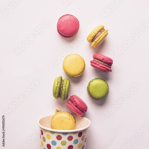Fotobehang Macarons Macarons out of a container on a white background