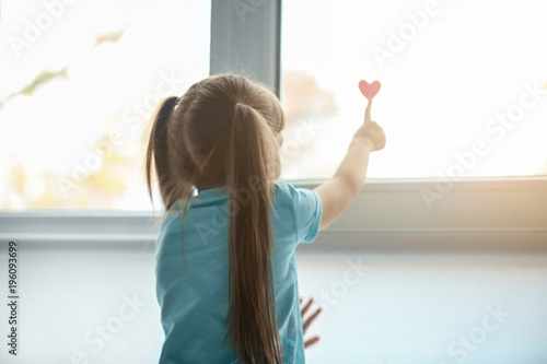 little-girl-with-red-heart-near-window-autism-concept