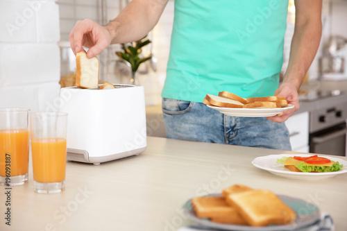Man toasting bread in kitchen