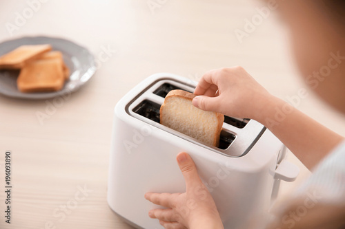 Little girl toasting bread at home