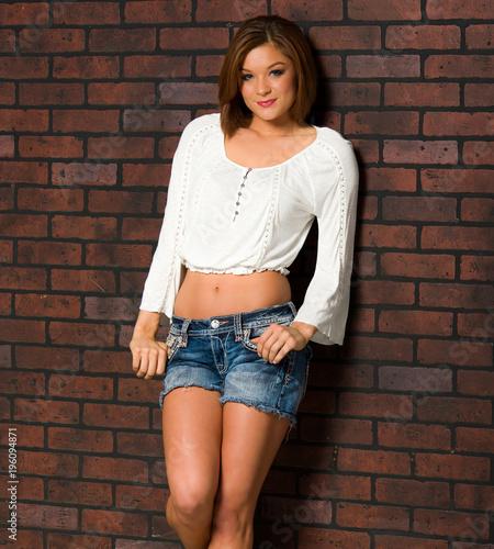 Fotografía  Beautiful Woman Leaning Against a Brick Wall