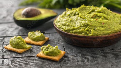 Fotografía  Half an avocado and a bowl of guacamole on rustic table