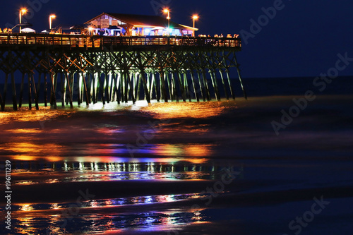 Night View With Glowing In The Dark Illumination At Atlantic Ocean Beach  Wooden Pier And Bright