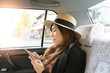 Asian woman is using smart phone while traveling in Japan inside Taxi Car.